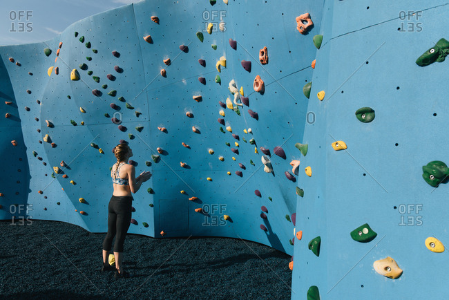 Young woman standing in front of climbing wall, Brooklyn Bridge Park, Brooklyn, New York, USA