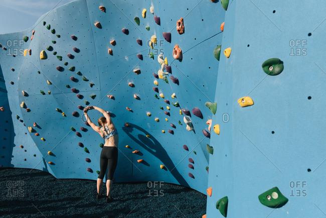 Young woman stretching, preparing to use climbing wall, Brooklyn Bridge Park, Brooklyn, New York, USA