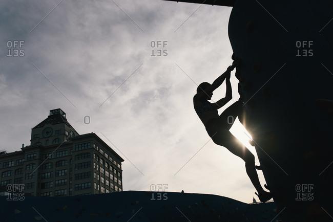 Young woman on climbing wall at sunset, Brooklyn Bridge Park, Brooklyn, New York, USA