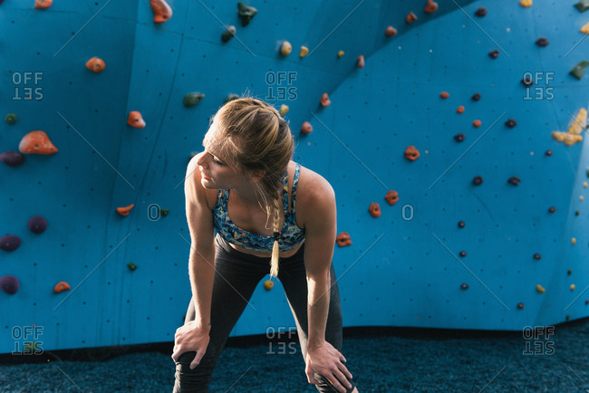 Young woman standing in front of climbing wall, hands on knees, Brooklyn Bridge Park, Brooklyn, New York, USA
