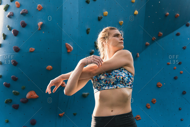 Young woman stretching in front of climbing wall, Brooklyn Bridge Park, Brooklyn, New York, USA
