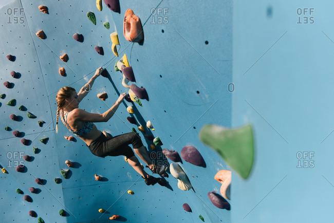 Young woman on climbing wall, Brooklyn Bridge Park, Brooklyn, New York, USA
