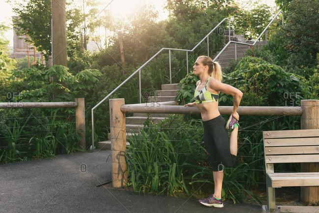 Young woman exercising outdoors, stretching leg, Brooklyn Bridge Park, Brooklyn, New York, USA