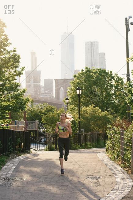 Young woman exercising outdoors, running, Brooklyn Bridge Park, Brooklyn, New York, USA