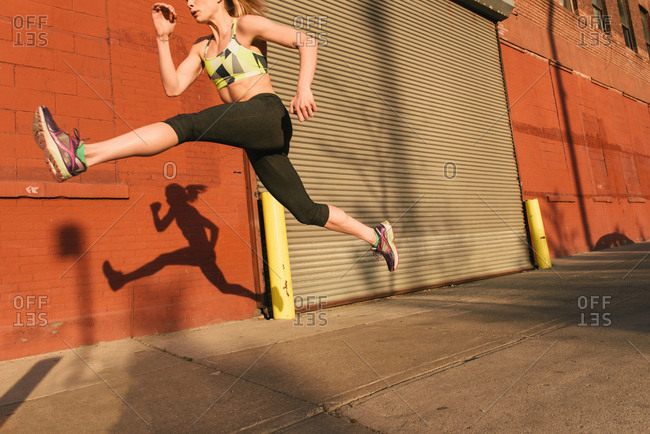 Young woman exercising outdoors, leaping through air, shadow beside her,  Brooklyn, New York, USA