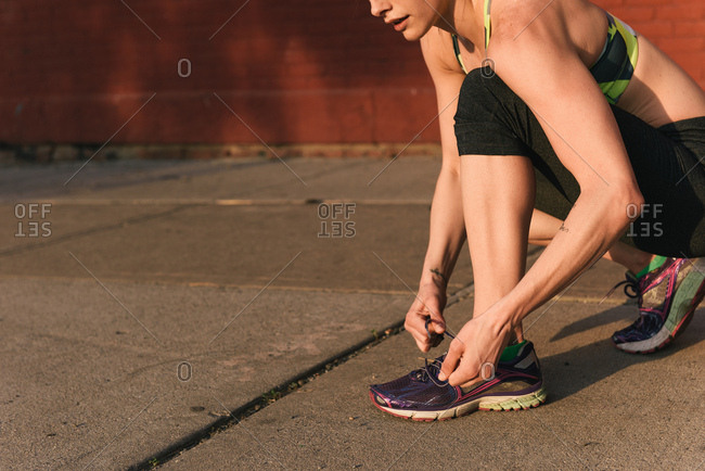 Young woman wearing sports clothing, crouching to tie shoelace, low section