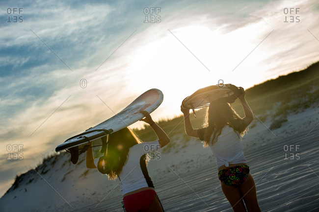 Two young girls in sea, holding surfboards, rear view