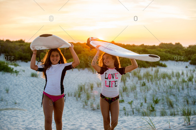 Two young girls on beach, carrying surfboards