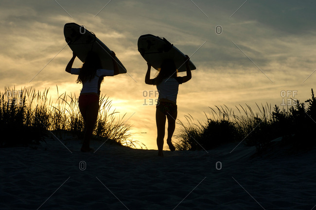 Two young girls on sand dunes, at dusk, carrying surfboards