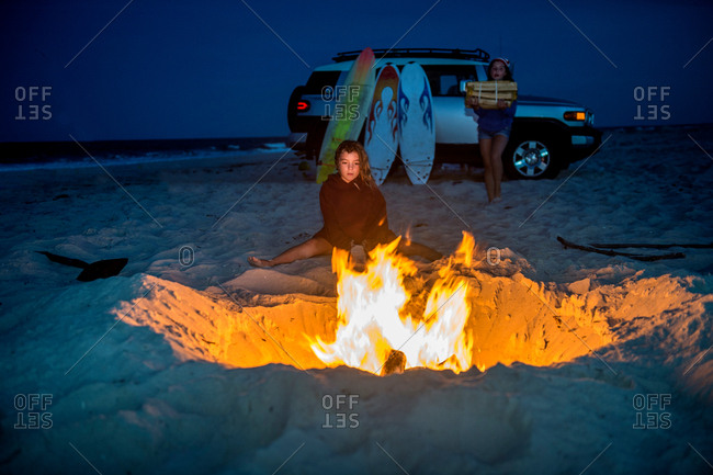 Young girl sitting by campfire on beach, her sister carrying fire wood towards fire