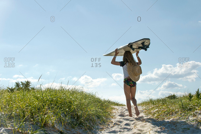 Young girl walking on sand dunes, carrying surfboard, rear view