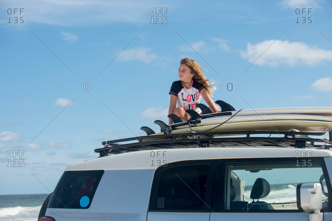 Young girl on top of car, looking at view
