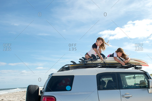 Two young girls securing surfboards to top of car