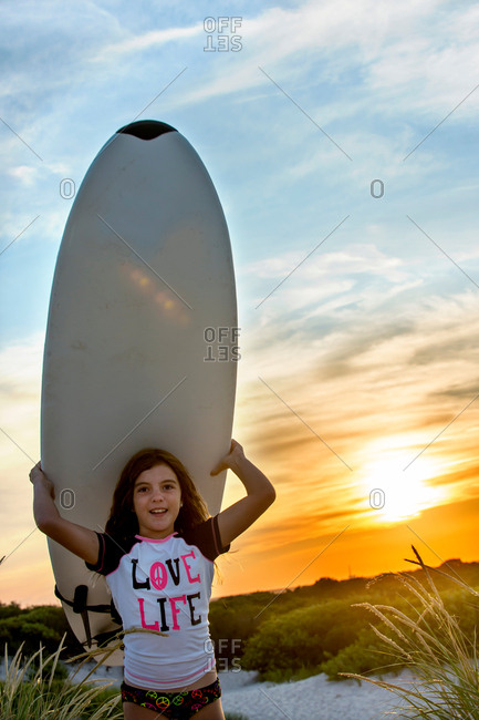 Young girl at beach, carrying surfboard, at sunset