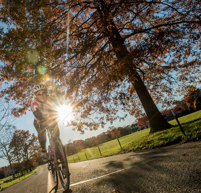 Angled view of cyclist cycling in sunlight