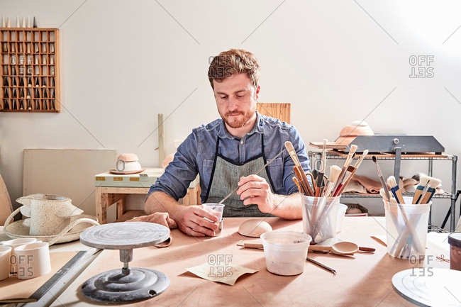 Man in workshop painting pottery