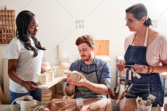 Group of people painting pottery in workshop