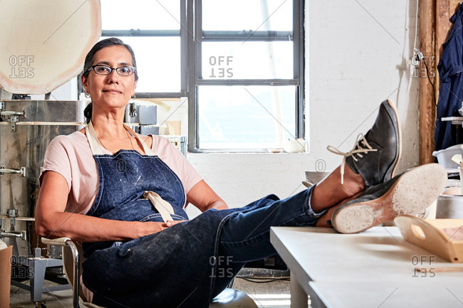 Woman sitting with feet up in pottery workshop