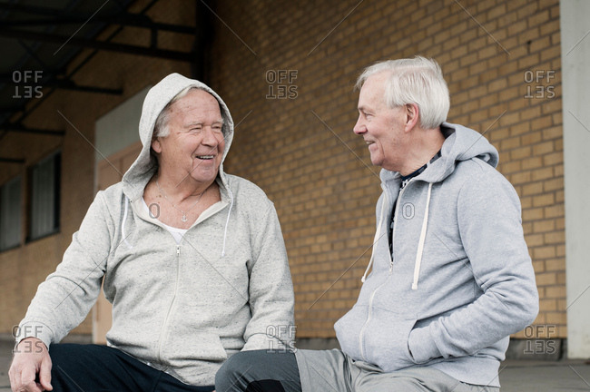 Senior friends wearing sports clothes sitting together