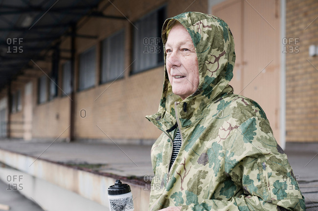 Man wearing camouflage waterproof hooded coat looking away