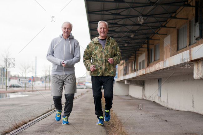 Senior friends wearing sports clothes jogging side by side