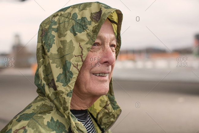 Man wearing camouflage waterproof hooded coat looking away