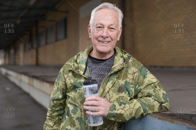 Man holding water bottle looking at camera smiling