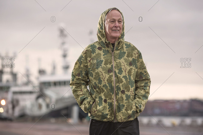 Man wearing waterproof hooded camouflage coat on dockland