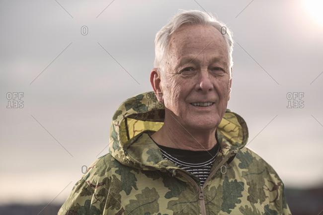 Man wearing waterproof hooded camouflage coat looking at camera
