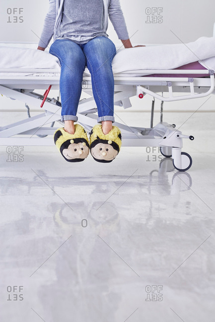 Low section of woman wearing bumblebee slippers sitting on hospital bed
