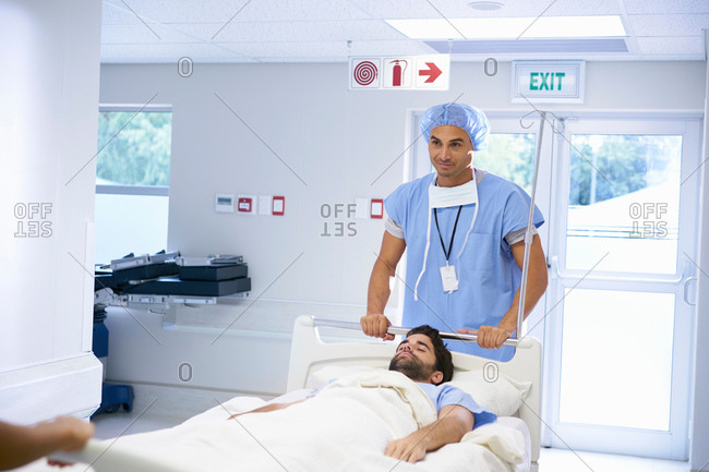 Doctors wearing surgical scrubs pushing patient on hospital bed