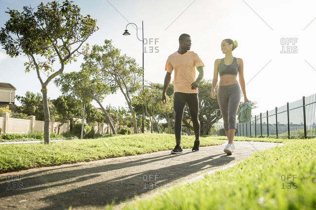 Couple wearing sports clothing walking on path