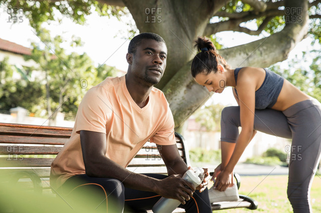 Man wearing sports clothes sitting on park bench looking away