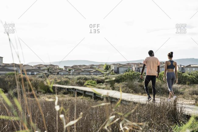 Rear view of couple walking on wooden walkway