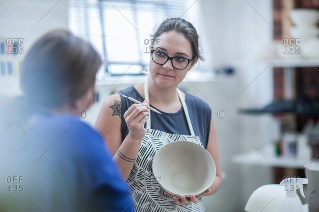 Female potter explaining finishing tool for bowl to trainee in workshop