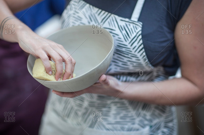 Cropped shot of female potter smoothing finished bowl in workshop