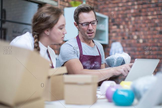Male potter explaining packing of online pot in workshop