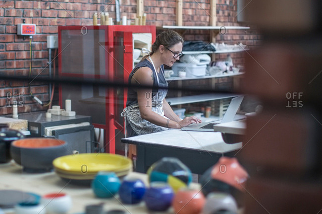 Female potter checking online orders in workshop