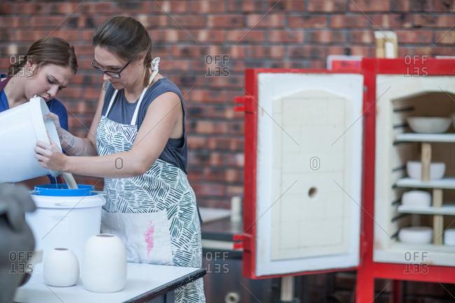 Female potter pouring ceramic glaze into bucket in workshop