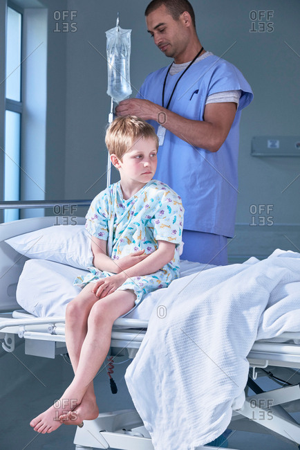 Male nurse adjusting boy patients intravenous drip in hospital children's ward