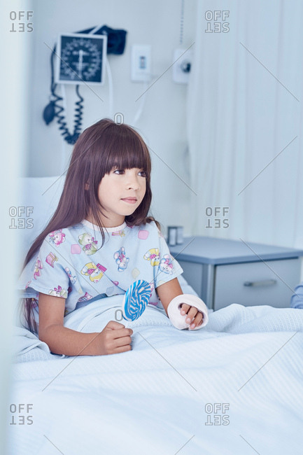 Girl patient with arm plaster cast  in bed with lollipop in hospital children's ward