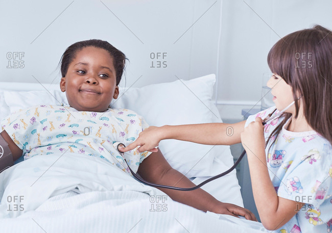 Girl patient using stethoscope on friend in bed on hospital children's ward