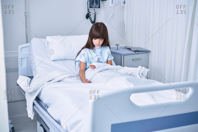 Girl patient in bed looking down at arm plaster cast in hospital children's ward