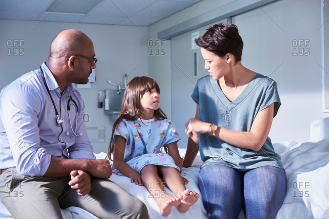 Male doctor explaining to girl patient and her mother in hospital children's ward