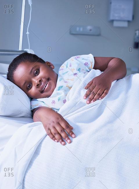 Portrait of girl patient in bed on hospital children's ward