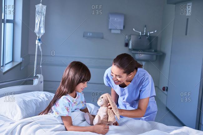 Nurse and girl patient playing with toy rabbit on hospital children's ward