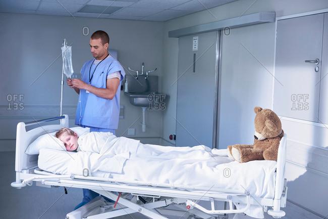 Male nurse adjusting intravenous drip for boy patient in hospital children's ward