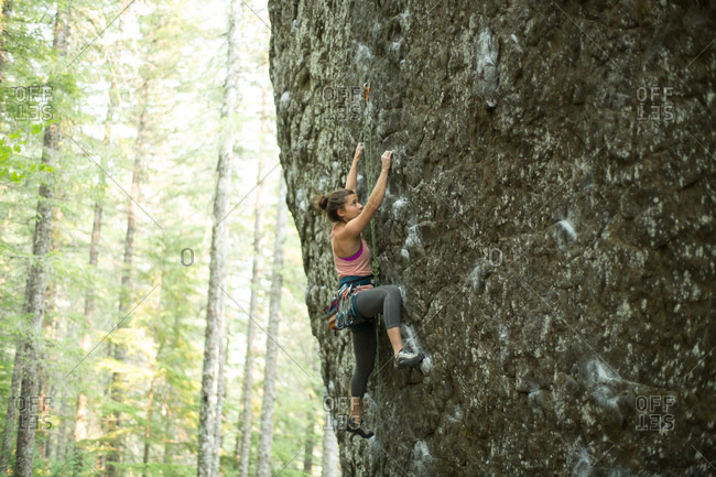 Young female rock climber climbing up rock face in forest, Mount Hood National Forest, Oregon, USA