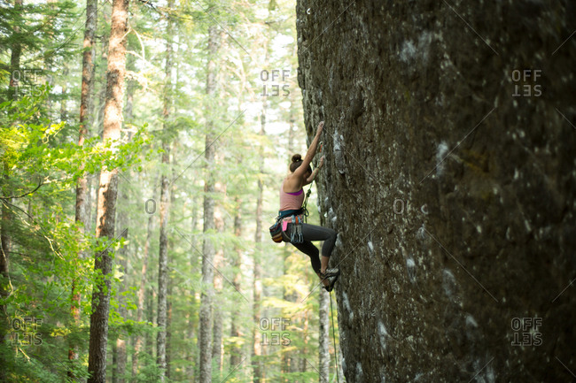 Young female rock climber climbing rock face in forest, Mount Hood National Forest, Oregon, USA