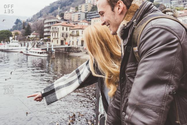 Happy young couple pointing at lake, Lake Como, Italy